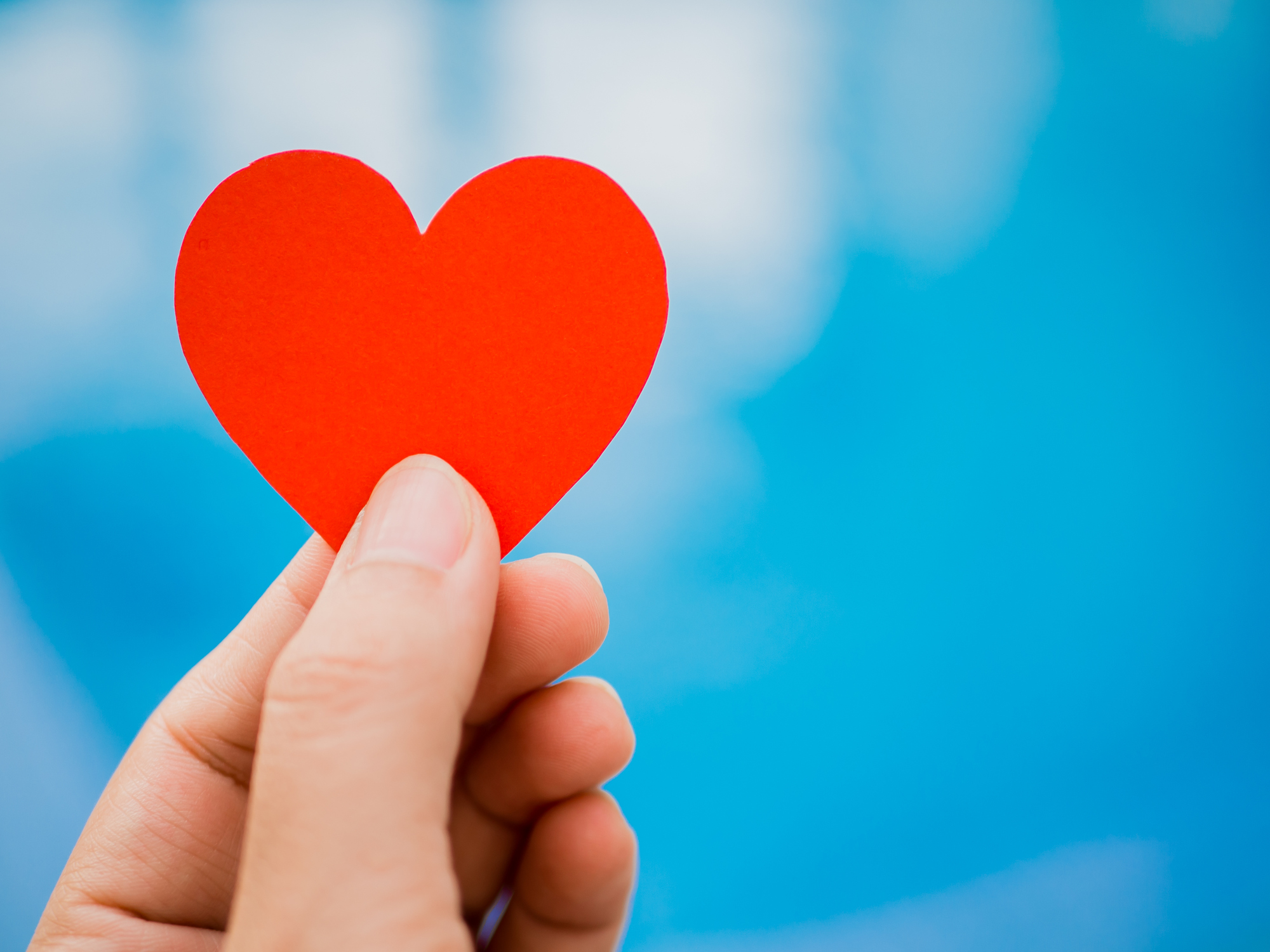 Closeup Hand Holding Red Paper Heart Shape On Blue Background Love